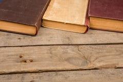 Alte Bücher oder Lehrbücher des gebundenen Buches auf Holztisch Lizenzfreie Stockfotos