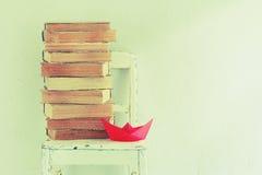 Alte Bücher, Stuhl und rotes Papierboot Lizenzfreies Stockbild