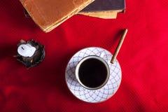 Alte Bücher, Tasse Kaffee, Zigarette und alte Kerze auf dem Re Stockfotografie