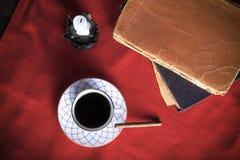 Alte Bücher, Tasse Kaffee, Zigarette und alte Kerze auf dem Re Lizenzfreies Stockfoto