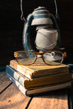 Alte Bücher und alte Laternenweinlese auf dem hölzernen Stockfoto