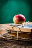 Alte Bücher und Apfel auf Schulbank Lizenzfreies Stockfoto