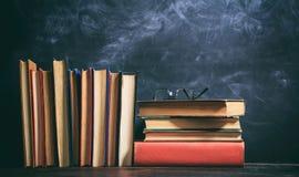 Alte Bücher und Augengläser auf Tafelhintergrund Lizenzfreies Stockfoto