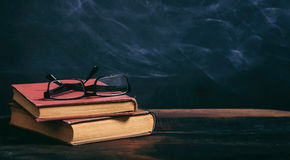 Alte Bücher und Augengläser auf Tafelhintergrund Stockbilder