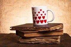 Alte Bücher und Becher mit vielen dargestellten Herzen auf dem alten hölzernen ta Lizenzfreies Stockfoto