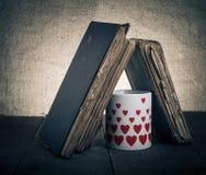 Alte Bücher und Becher mit vielen dargestellten Herzen auf dem alten hölzernen ta Lizenzfreie Stockfotografie