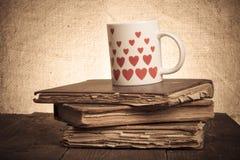 Alte Bücher und Becher mit vielen dargestellten Herzen auf dem alten hölzernen ta Stockbilder