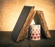 Alte Bücher und Becher mit vielen dargestellten Herzen auf dem alten hölzernen ta Stockfotografie