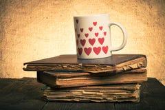 Alte Bücher und Becher mit vielen dargestellten Herzen auf dem alten hölzernen ta Lizenzfreie Stockfotos