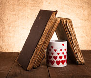Alte Bücher und Becher mit vielen dargestellten Herzen auf dem alten hölzernen ta Stockbild