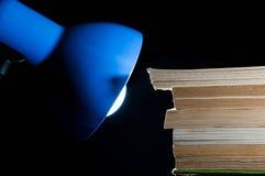 Alte Bücher und blaue Schreibtischlampe auf schwarzem Hintergrund Lizenzfreie Stockbilder