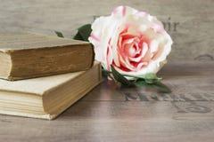 Alte Bücher und Blume stiegen auf einen hölzernen Hintergrund Romantischer Blumenrahmenhintergrund Bild, das von den Blumen liege Stockfoto