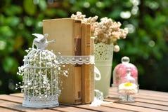 Alte Bücher und Blumen auf hölzerner Tabelle als Dekorationen für die Heirat des sonnigen Tages Stockfotografie