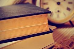 Alte Bücher und ein alter Wecker, mit einem Retro- Effekt Lizenzfreie Stockfotos