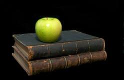 Alte Bücher und ein Apfel Lizenzfreie Stockfotos