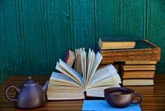 Alte Bücher und ein offenes Buch mit einer Schale und einem Kessel auf dem Tisch Stockbild