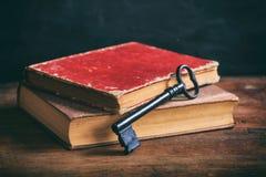 Alte Bücher und ein Schlüssel auf einem hölzernen Schreibtisch Stockfotografie