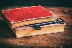 Alte Bücher und ein Schlüssel auf einem hölzernen Schreibtisch Lizenzfreie Stockfotos