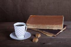 Alte Bücher und ein Tasse Kaffee mit zwei Süßigkeiten auf einem alten hölzernen Lizenzfreies Stockbild