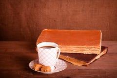 Alte Bücher und ein Tasse Kaffee mit zwei Süßigkeiten auf einem alten hölzernen Lizenzfreies Stockfoto
