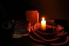 Alte Bücher und eine brennende Kerze Stockfotografie