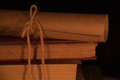 Alte Bücher und eine Rolle auf einem Holztisch auf einer Nacht Stockfotos