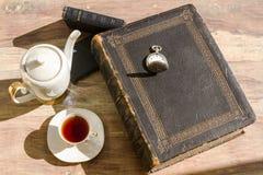 Alte Bücher und eine Tasse Tee Stockbilder