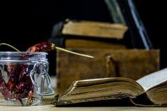 Alte Bücher und Gewürze Getrocknete Pfeffer und Rezepte Alte Küchetabelle Lizenzfreie Stockbilder