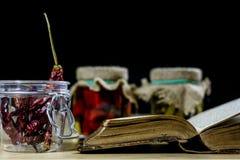 Alte Bücher und Gewürze Getrocknete Pfeffer und Rezepte Alte Küchetabelle Stockfoto