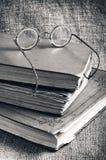 Alte Bücher und Gläser auf einem Hintergrund des Jutefasers Lizenzfreies Stockfoto