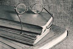 Alte Bücher und Gläser auf einem Hintergrund des Jutefasers Stockfotografie