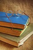 Alte Bücher und Gläser auf einem Hintergrund des Jutefasers Lizenzfreie Stockfotos