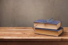 Alte Bücher und Gläser auf Holztisch über rustikalem Hintergrund Ausbildung Stockfotos