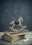 Alte Bücher und hölzernes Spielzeugpferd Stockbild