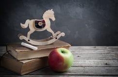 Alte Bücher und hölzernes Spielzeugpferd Stockbilder