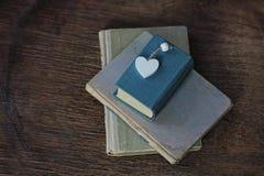 Alte Bücher und Herz, die auf einer Holzoberfläche liegt Stockbild