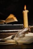 Alte Bücher und Kerzen auf Holztisch Lizenzfreie Stockbilder