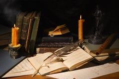 Alte Bücher und Kerzen auf Holztisch Stockbilder
