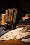 Alte Bücher und Kerzen auf Holztisch Stockfoto