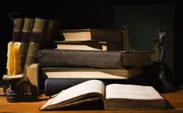Alte Bücher und Kerzen auf Holztisch Lizenzfreie Stockfotos