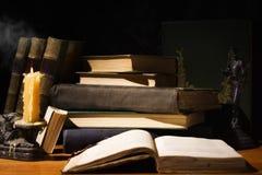 Alte Bücher und Kerzen auf Holztisch Stockfotografie