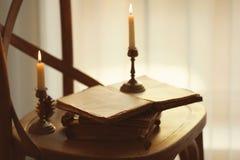 Alte Bücher und Kerzen auf Stuhl Stockbild