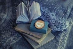 Alte Bücher und Lügen eines hölzerne Herzens auf einer Strickjacke Kalter Ton Hintergrund Weicher Fokus Lizenzfreies Stockfoto