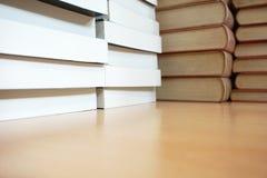 Alte Bücher und neue Bücher gestapelt oben auf dem hölzernen Schreibtisch lizenzfreie stockfotografie