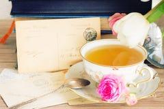 Alte Bücher und Post mit Tasse Tee Stockfotografie