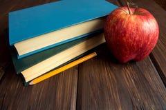 Alte Bücher und roter Apfel Stockbilder