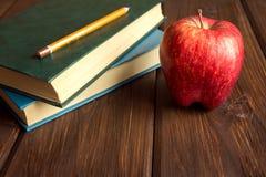 Alte Bücher und roter Apfel Stockbild