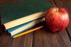 Alte Bücher und roter Apfel Lizenzfreies Stockfoto