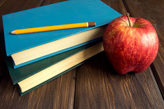 Alte Bücher und roter Apfel Stockfoto