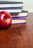 Alte Bücher und roter Apfel auf Holztisch Stockfotos